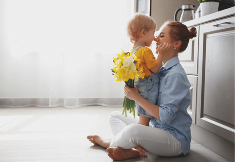 A mother and child sit on the floor of a clean room